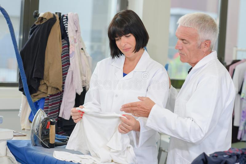 Man and woman inspecting garment. Man and women inspecting garment inspect stock photo