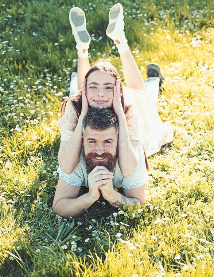 Man and woman laying on grass spring day. Spring leisure concept. Couple on happy smiling faces laying at meadow, nature. Man and women laying on grass spring stock images