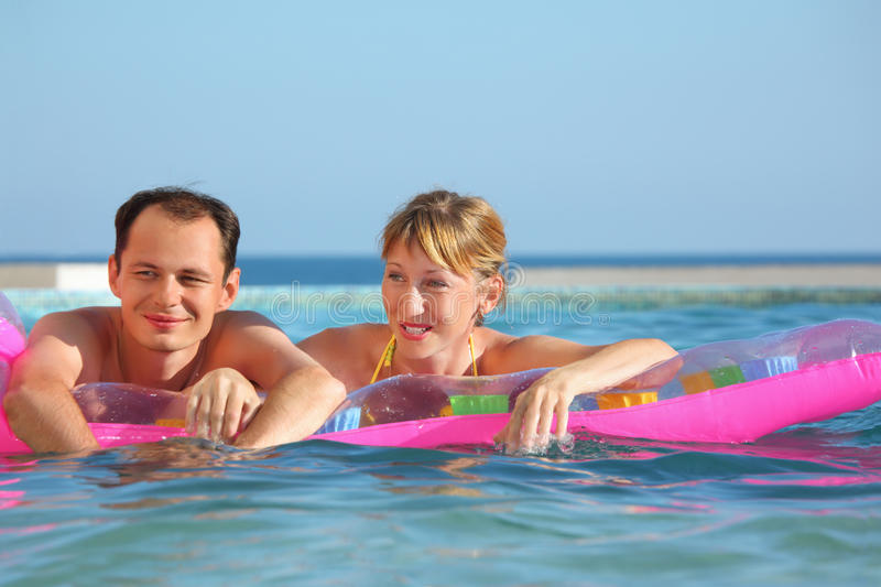 Download Man And Women Lying On An Mattress In Pool Stock Photo - Image: 13021890