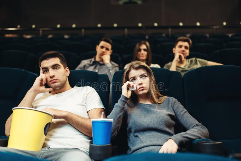 Boring film concept, couple watching movie. Man and women with popcorn in cinema. Boring film concept, couple watching movie royalty free stock image