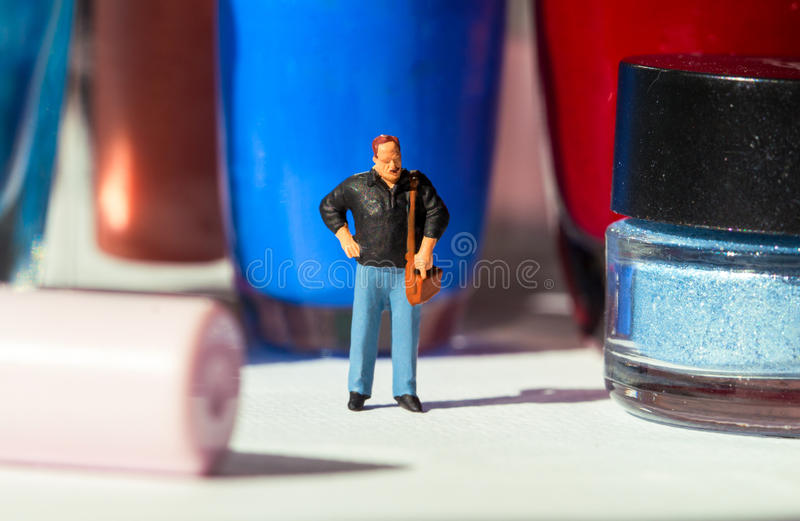 Man and women`s nail polish. Husband miniature figure in decorative cosmetic land. royalty free stock image
