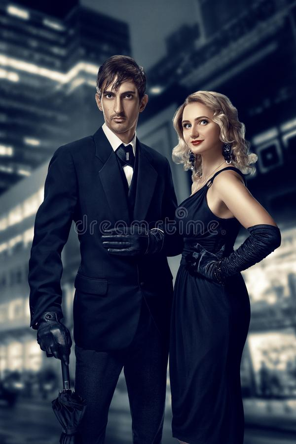 Man and woman secret agents and spies. Film noir. Retro style fashion portraits against the backdrop of the night city stock photos