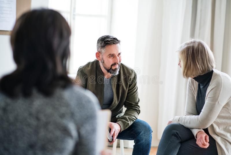 Man and women sitting in a circle during group therapy, talking. royalty free stock images