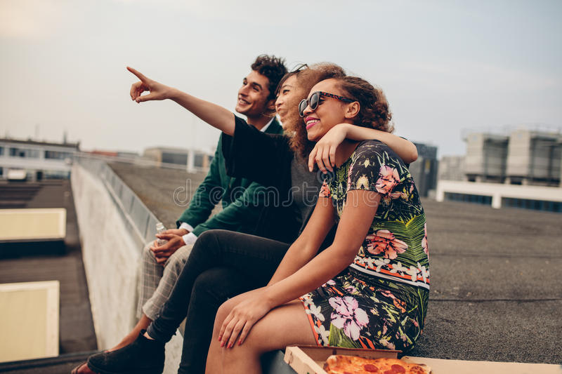 Man and women sitting on roof terrace. And looking away smiling. Happy young friends relaxing on rooftop, with women pointing at something interesting stock photos