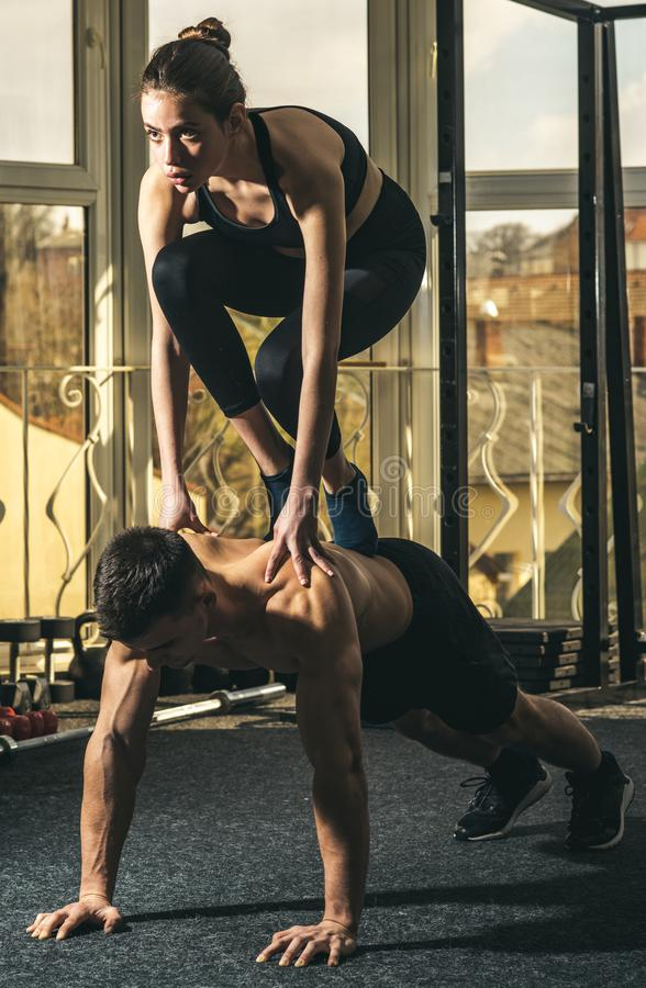 Man and woman in sportswear in gym, window on background. Couple does acroyoga, physical practice of yoga and acrobatics royalty free stock photography