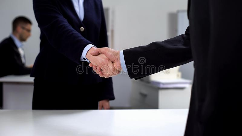 Man and woman in suits shaking hands at workplace, business deal, cooperation. Man and women in suits shaking hands at workplace, business deal, cooperation stock photos