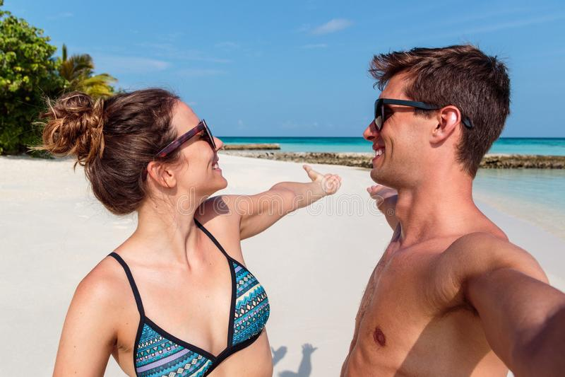 Happy young couple taking a selfie, tropical island and clear blue water as background. Man and women in .swimsuit taking a self portrait picture during holiday royalty free stock image