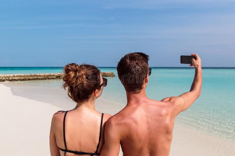 Happy young couple taking a selfie. Tropical island as background. Man and women in .swimsuit taking a self portrait picture during holiday. turquoise water as stock photos