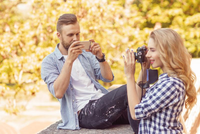 Man and woman taking photos with a camera and a smartphone in autumn park. royalty free stock photography