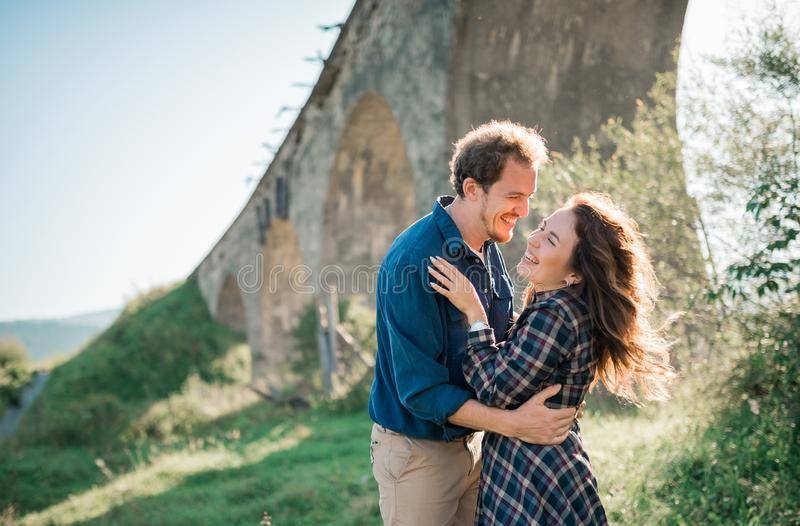 Happy joyfull young couple laughing outdoors at sunset royalty free stock photography