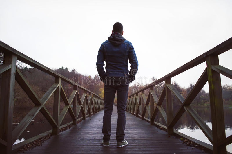 Man on wooden bridge over a lake, on a damp autumn day. Deep perspective of a man standing on a wooden pedestrian bridge crossing a lake. A hazy, damp autumn royalty free stock image