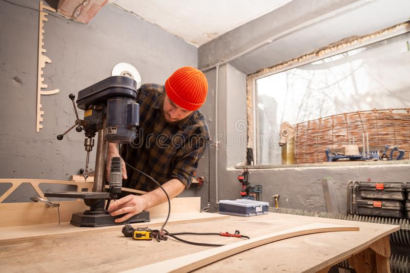 Experienced carpenter work in workshop. A man with work clothes and a carpenter`s cap is carving a wooden board on an modern large drilling machine in a light royalty free stock photos