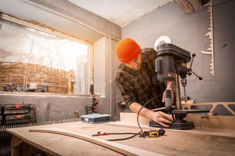 Experienced carpenter work in workshop. A man with work clothes and a carpenter`s cap is carving a wooden board on an modern large drilling machine in a light royalty free stock photo