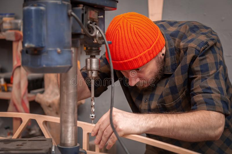 Experienced carpenter work in workshop. A man with work clothes and a carpenter`s hat is carving a wooden board on an  large drilling machine in a light workshop stock photography