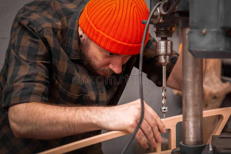 Experienced carpenter work in workshop. A man with work clothes and a carpenter`s hat is carving a wooden board on an  large drilling machine in a light workshop stock photo
