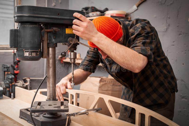Experienced carpenter work in workshop. A man with work clothes and a carpenter`s hat is carving a wooden board on an  large drilling machine in a light workshop royalty free stock photography