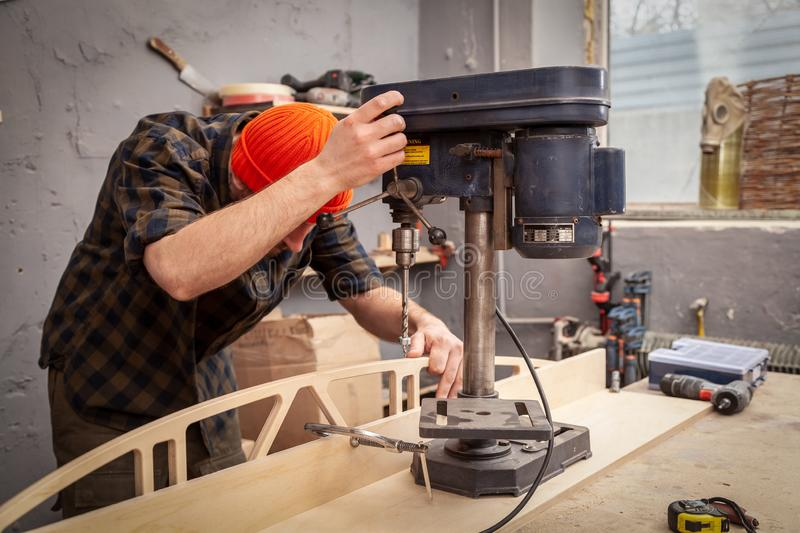 Experienced carpenter work in workshop. A man with work clothes and a carpenter`s hat is carving a wooden board on an  large drilling machine in a light workshop royalty free stock image