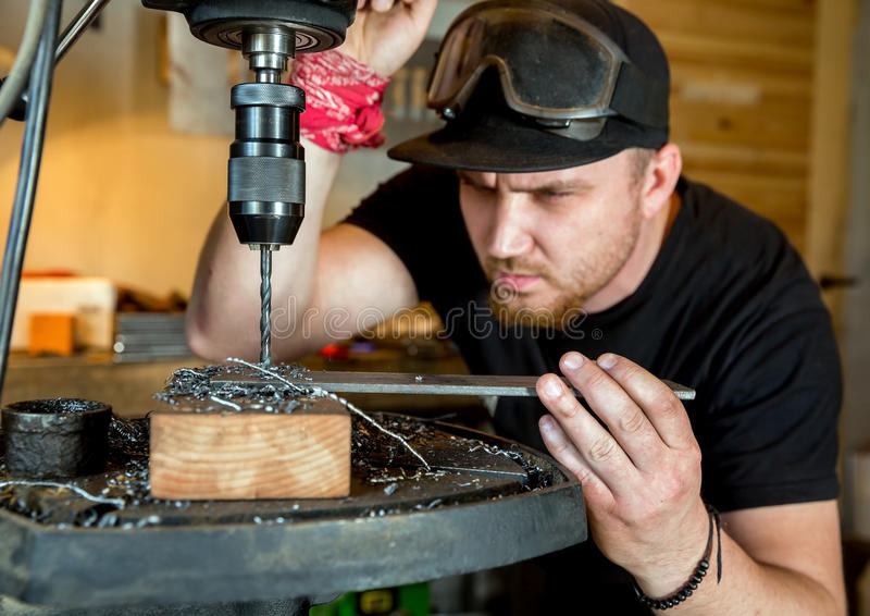 Man in work on electric drill press. Electric drilling machine with manual pressure, a man holding a metal part and the hole is drilled, strongly pressing drill stock photo