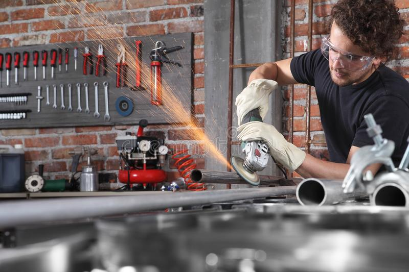Man work in home workshop garage with angle grinder, goggles and construction gloves, grinder metal makes sparks, diy and craft. Concept stock image