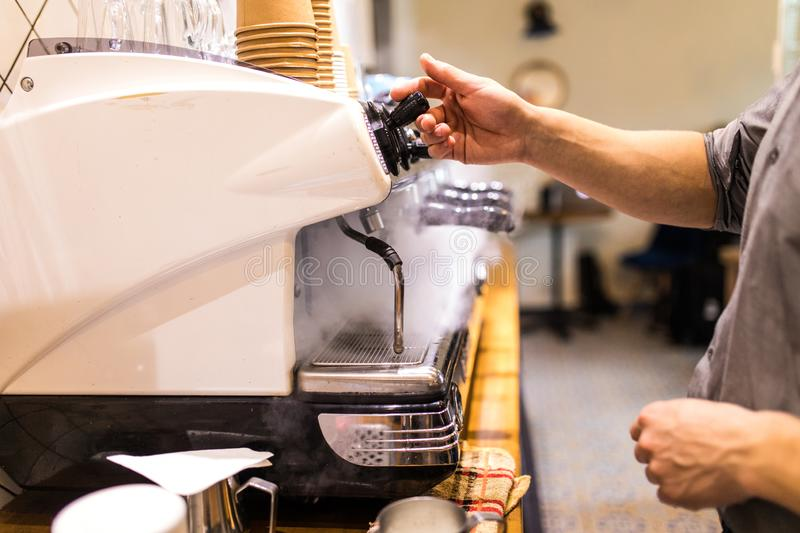 Young Man hands work near coffee-maker in coffee shop. Air compressing. Man work near coffee-maker in coffee shop. Air steam royalty free stock photo