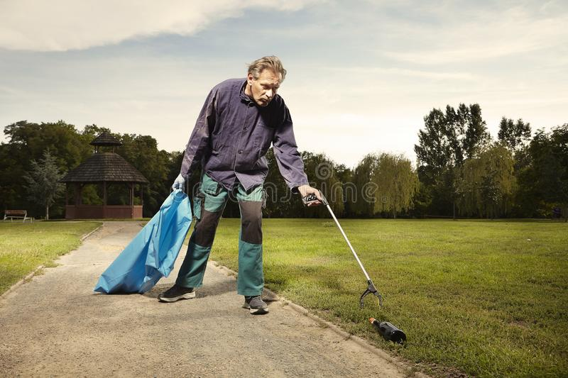Man at work pick up garbage on grass in park stock images