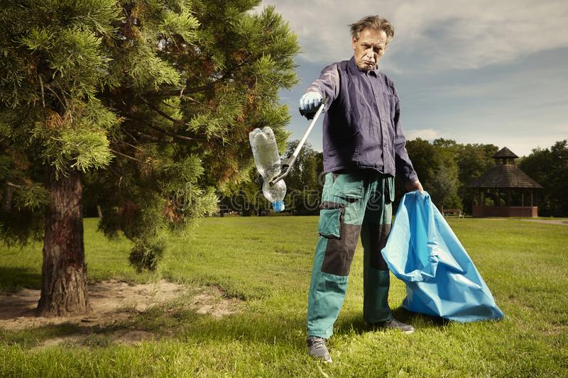 Man at work pick up garbage on grass in park royalty free stock photography