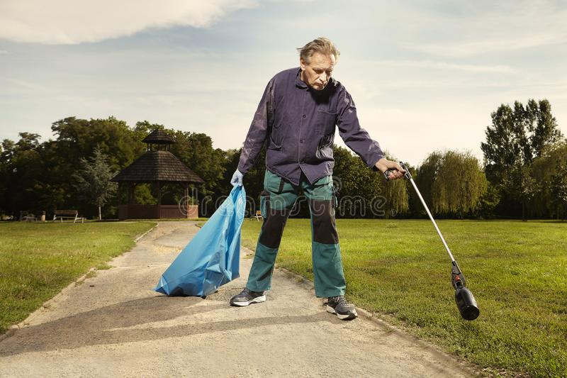Man at work pick up garbage on grass in park royalty free stock images