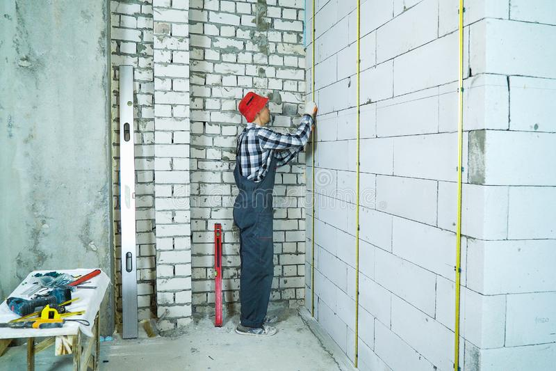 Man in work wear installing metal rails onto aerated concrete block wall. Construction worker at house renovation site. safety at work, danger and industry stock image