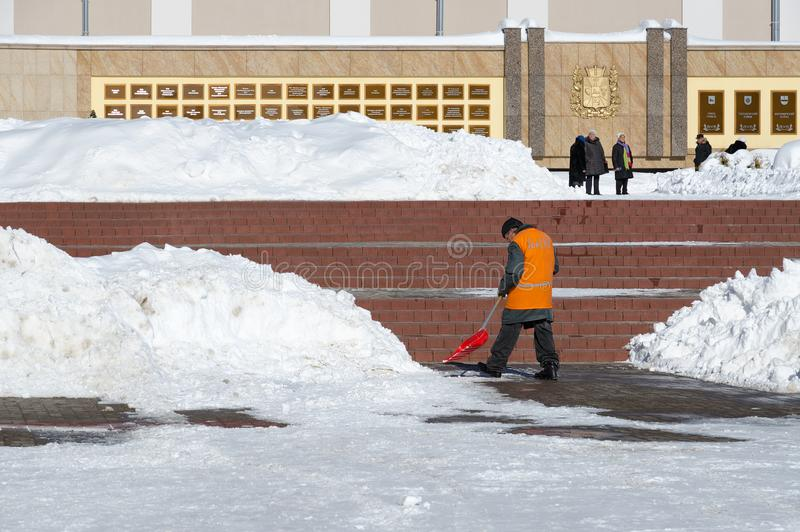 Man worker of communal service in orange special clothes cleans street in center of city from snow after heavy snowfall in March. GOMEL, BELARUS - MARCH 5, 2018 stock photos
