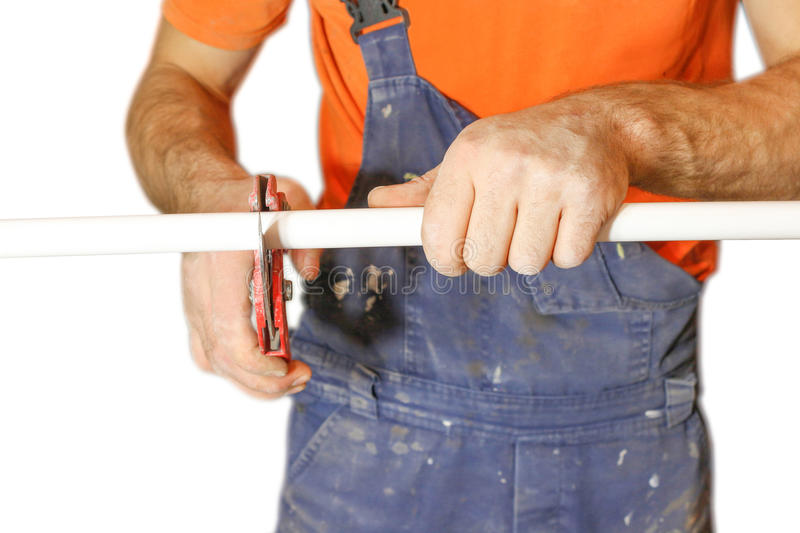 Man worker cuts off a piece of polypropylene pipes. Isolated on. White background royalty free stock photos