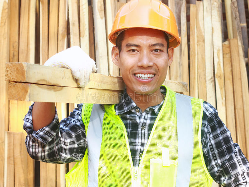 Man worker with helmet and safety vest carrying wood royalty free stock images