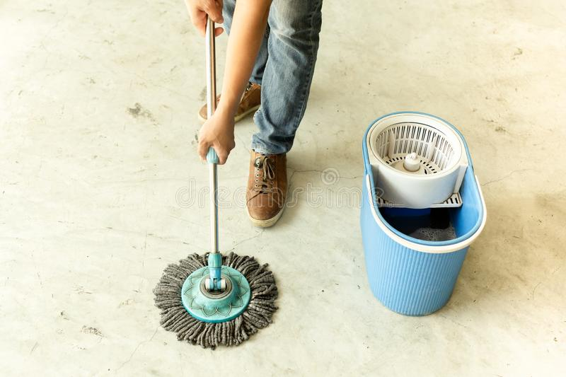 Man worker with mop cleaning floor in the cafe. stock image