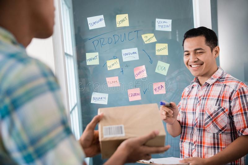 A man worker pointing to the box held by his partner for examples a good package with a address. A men worker pointing to the box held by his partner for royalty free stock photography