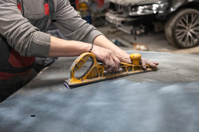 Man worker preparing for painting a car element using emery sender by a service technician leveling out before applying a primer stock images