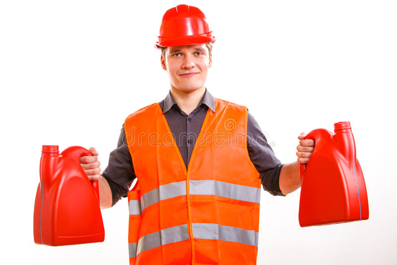 Man worker in safety vest hard hat with canisters. Young man construction worker in orange safety vest and red hard hat holding plastic canisters isolated on royalty free stock images