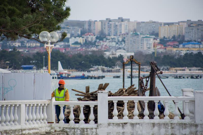 Man worker in special clothes and yellow helmet stands on city promenade where repair is against sea and urban landscape. With residential high houses royalty free stock photography