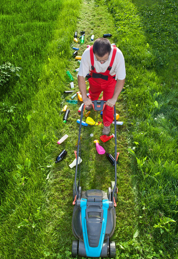 Man working against nature - concept with plastic spewing lawn m. Ower, view from above royalty free stock photography