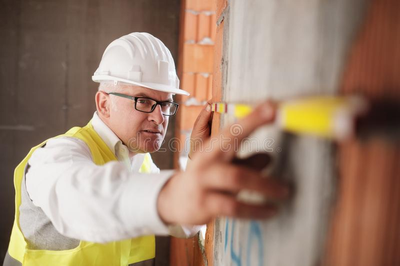 Man Working As Architect Measuring Wall In Construction Site royalty free stock photos