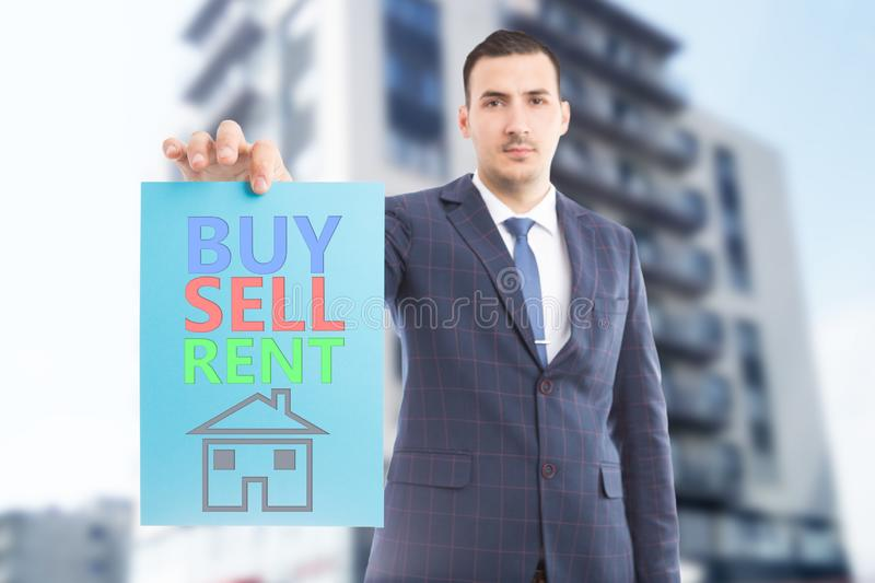 Man presenting buy sell rent paper with house drawing stock images