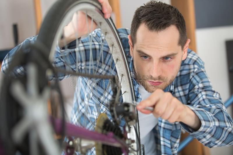 Man working on bicycle chain royalty free stock photos
