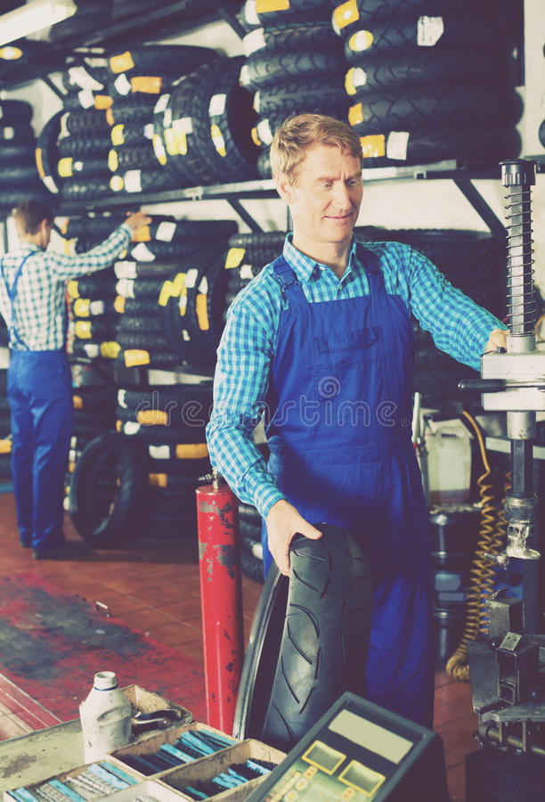 Man working with bike tires. Cheerful adult men working with bike tires in tire shop stock photo
