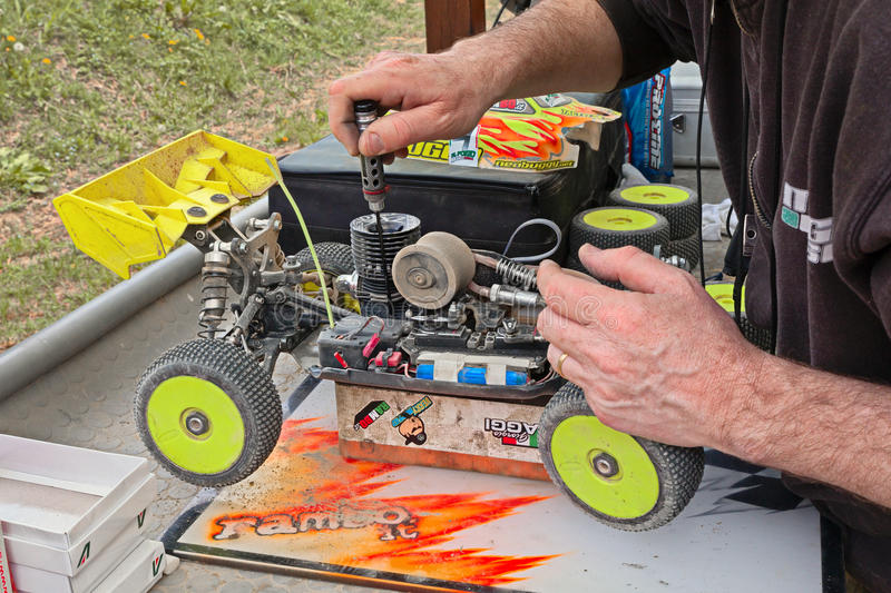 Man working on the buggy car model. Man working on the radio controlled buggy car model, internal combustion engine, in regional championship scale 1/8 off road royalty free stock image