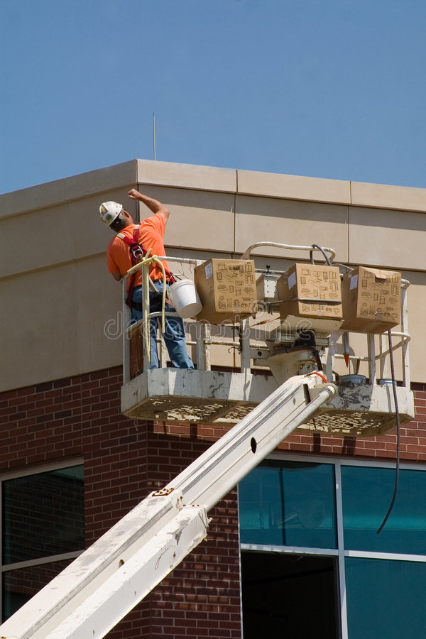 Man working on building. This is a picture of a man standing in a lift bucket working high above the ground. He's applying grout at the top of a new building. He stock photos