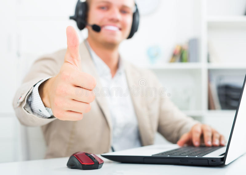 Man working in call centre. Portrait of positive young man with headphones working in call centre royalty free stock images