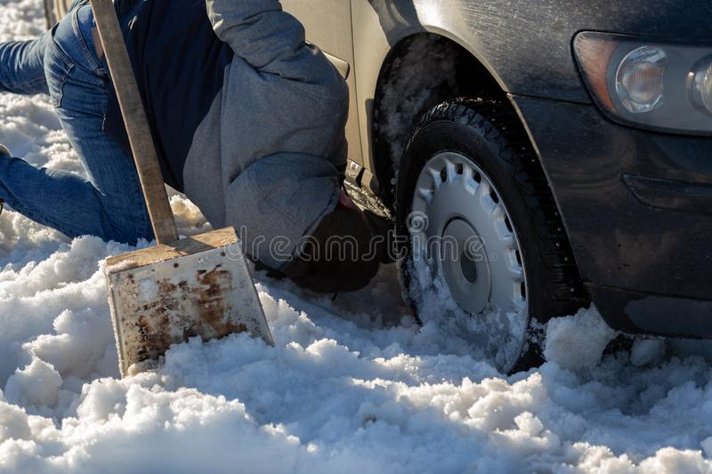 Man working at car stuck in snow on knee with shovel at daylight offroad.  stock photos