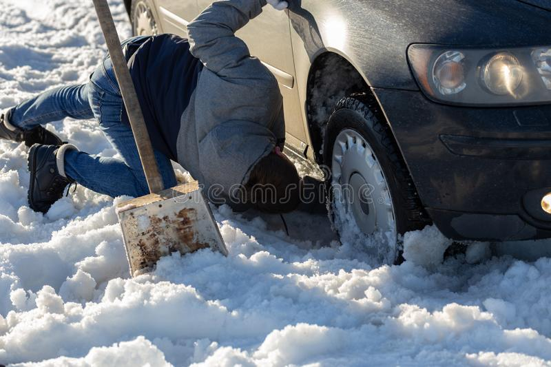 Man working at car stuck in snow on knee with shovel at daylight offroad.  stock image