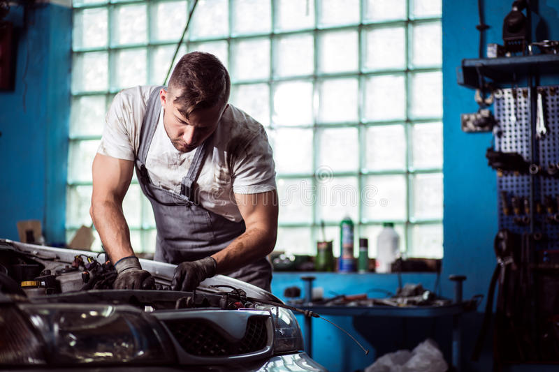 Man working in car workshop stock images