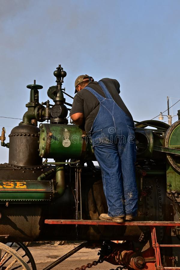 Man working on a Case steam engine. ROLLAG, MINNESOTA, Sept 1. 2017: An unidentified man is inspecting an old Case steam engine at the annual WCSTR farm show in stock photography