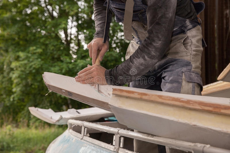 Man working with a chisel. Close up of a man working with a chisel in a garage royalty free stock image