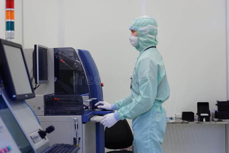 Man working in clean room at JCS Avangard, St. Petersburg. St. Petersburg, Russia - April 18, 2016: Man in cleanroom suite working in clean room at JSC Avangard stock images